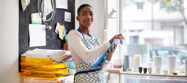 Une femme souriante tient une tablette devant un bureau