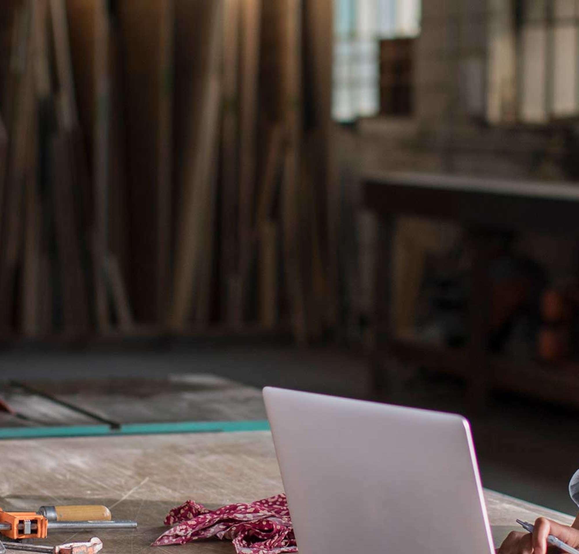 Une jeune femme travaillant sur un ordinateur portable dans son atelier de menuiserie.