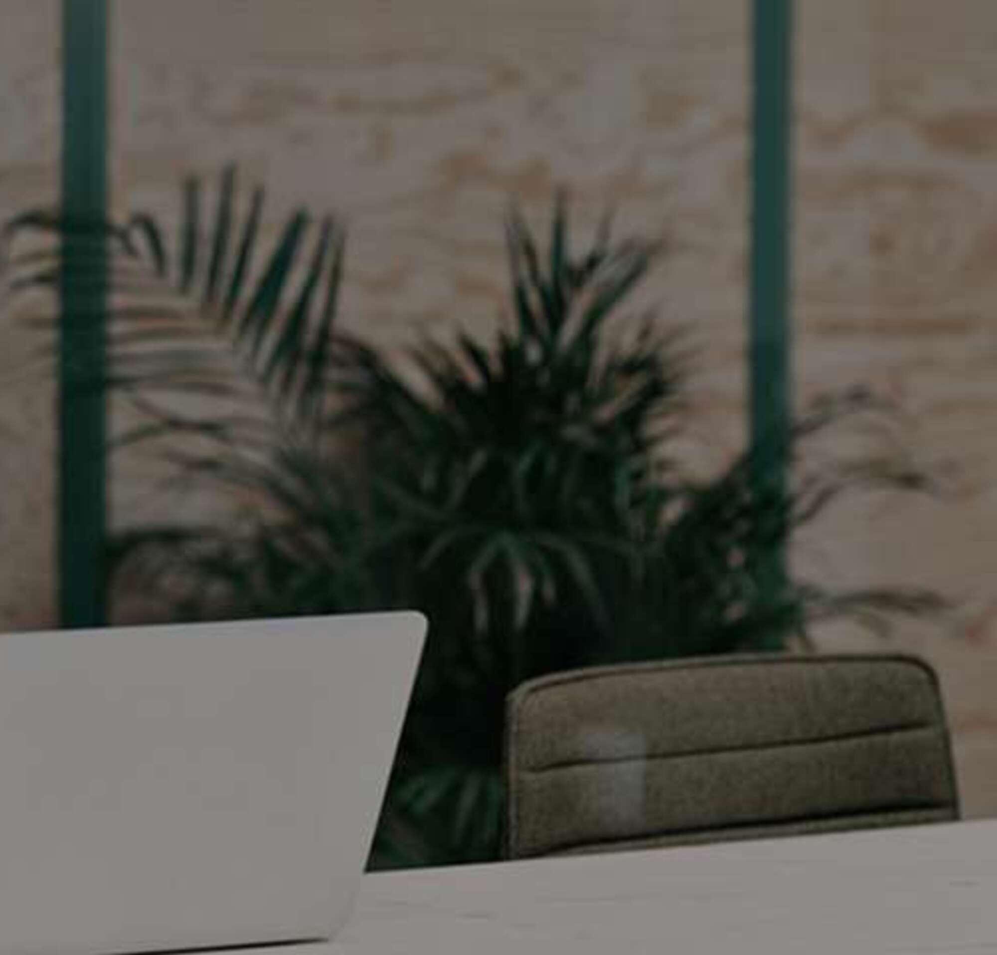 Une femme avec des écouteurs travaille sur un ordinateur portable en tenant son téléphone à la main.