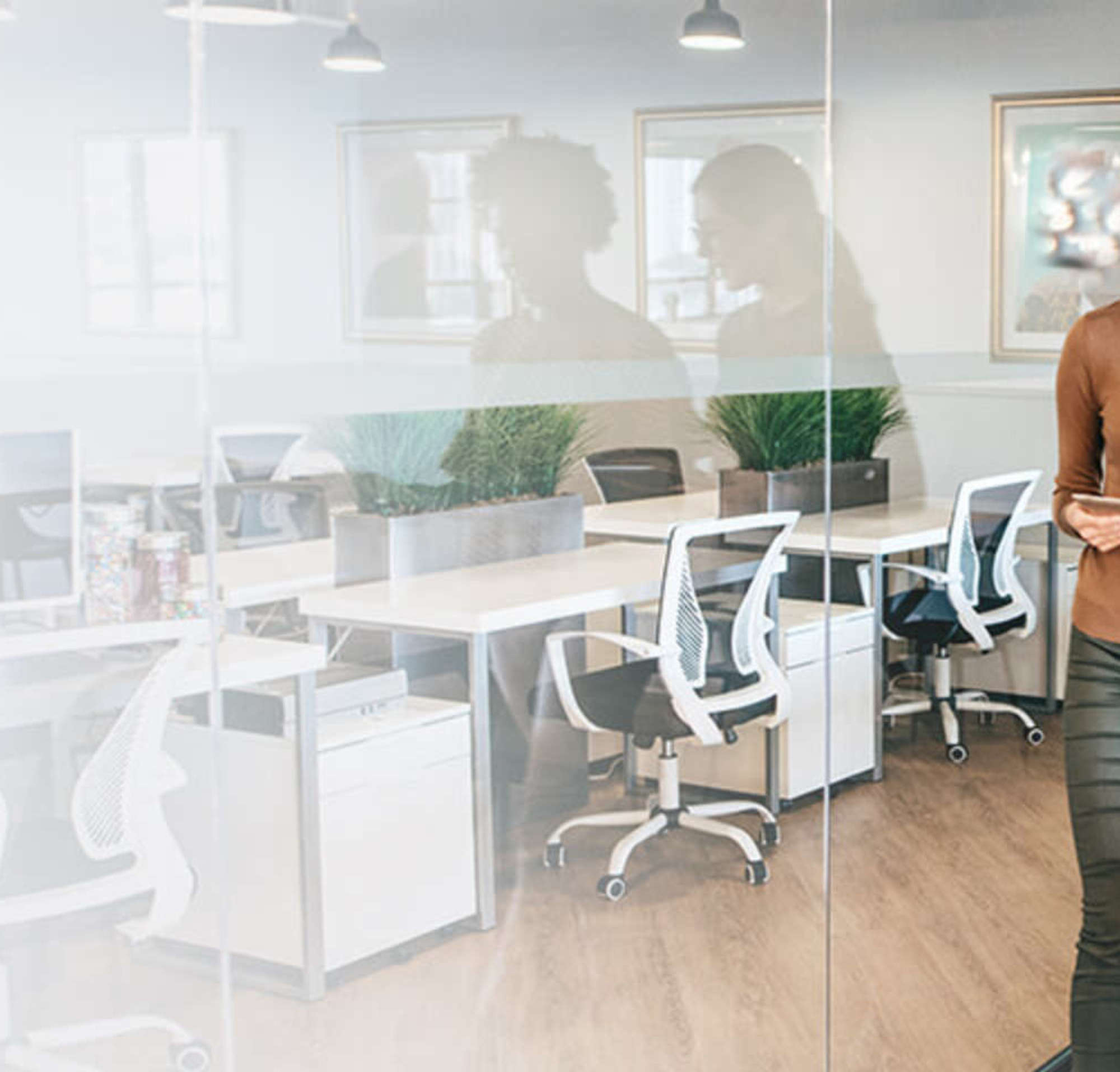Deux femmes dans une salle de réunion qui échangent tout en regardant un document.