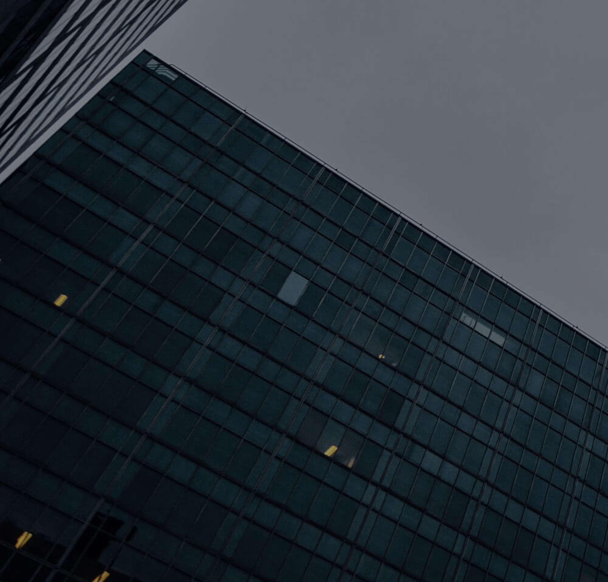 Une photo d'un gratte-ciel et d'un autre immeuble dans la lumière du soir.