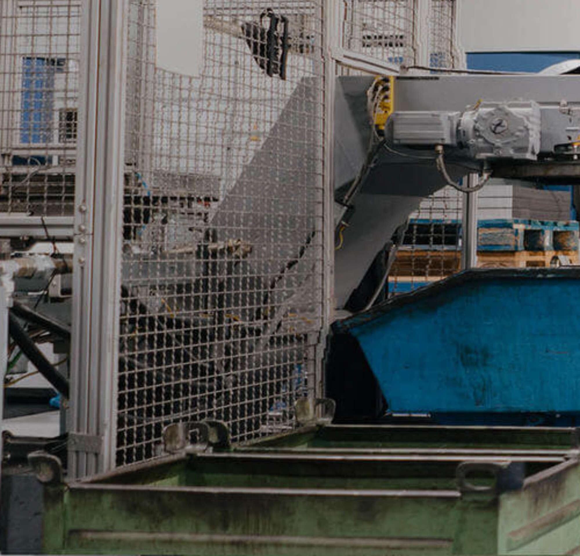 Un homme en costume et un ouvrier entre dans une usine avec de grosses machines.