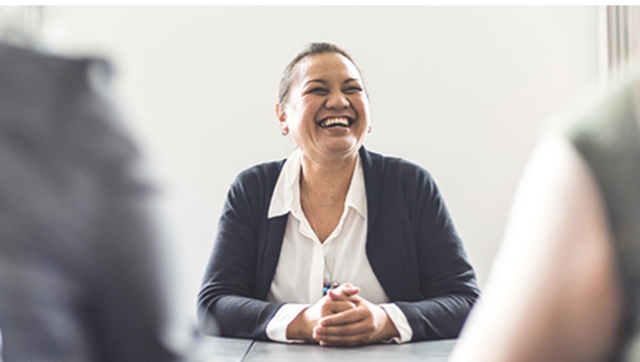Une femme d'affaire sourit à des clients depuis son bureau.