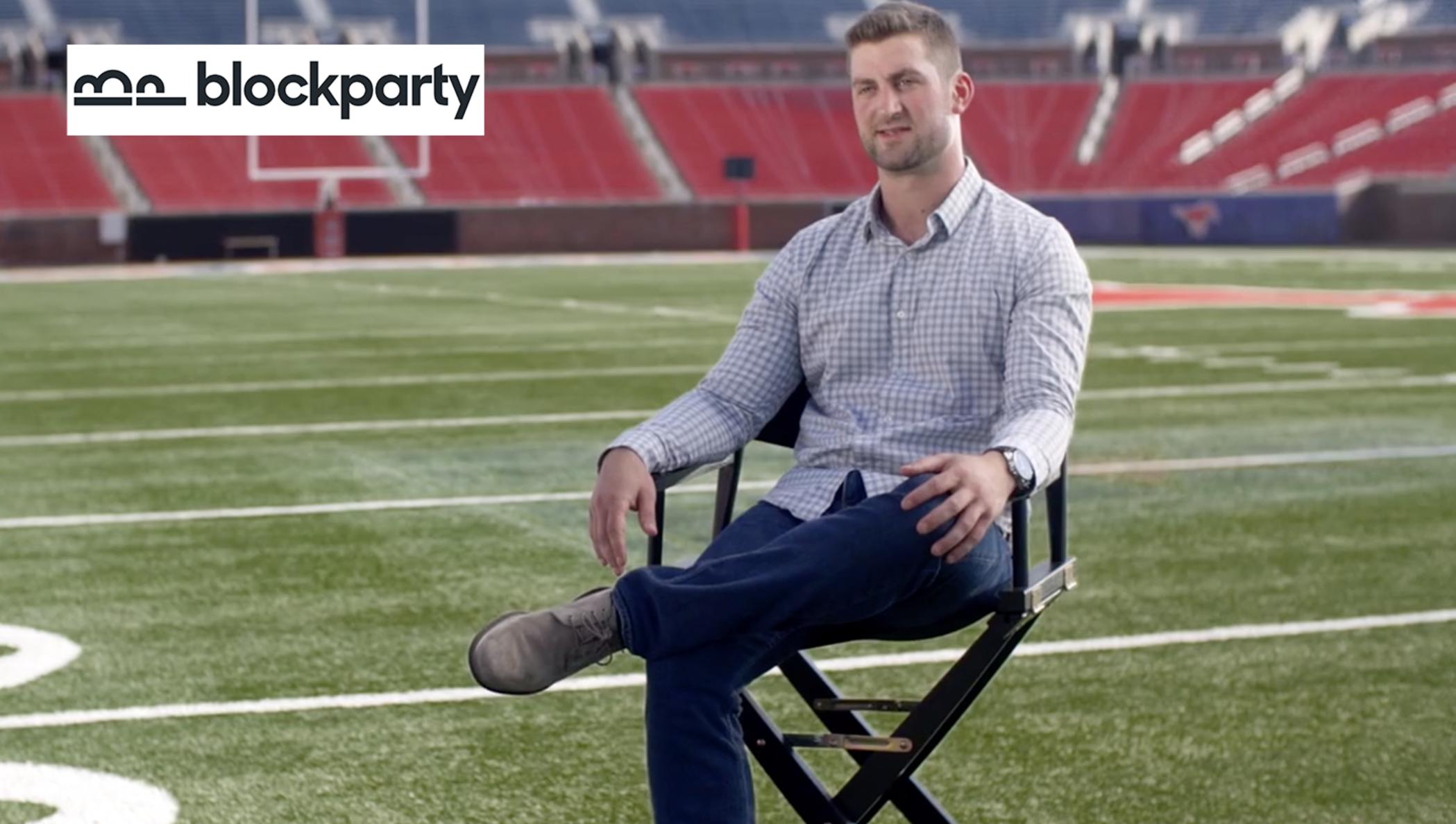 Un homme sur une chaise de réalisateur sur un terrain de football.