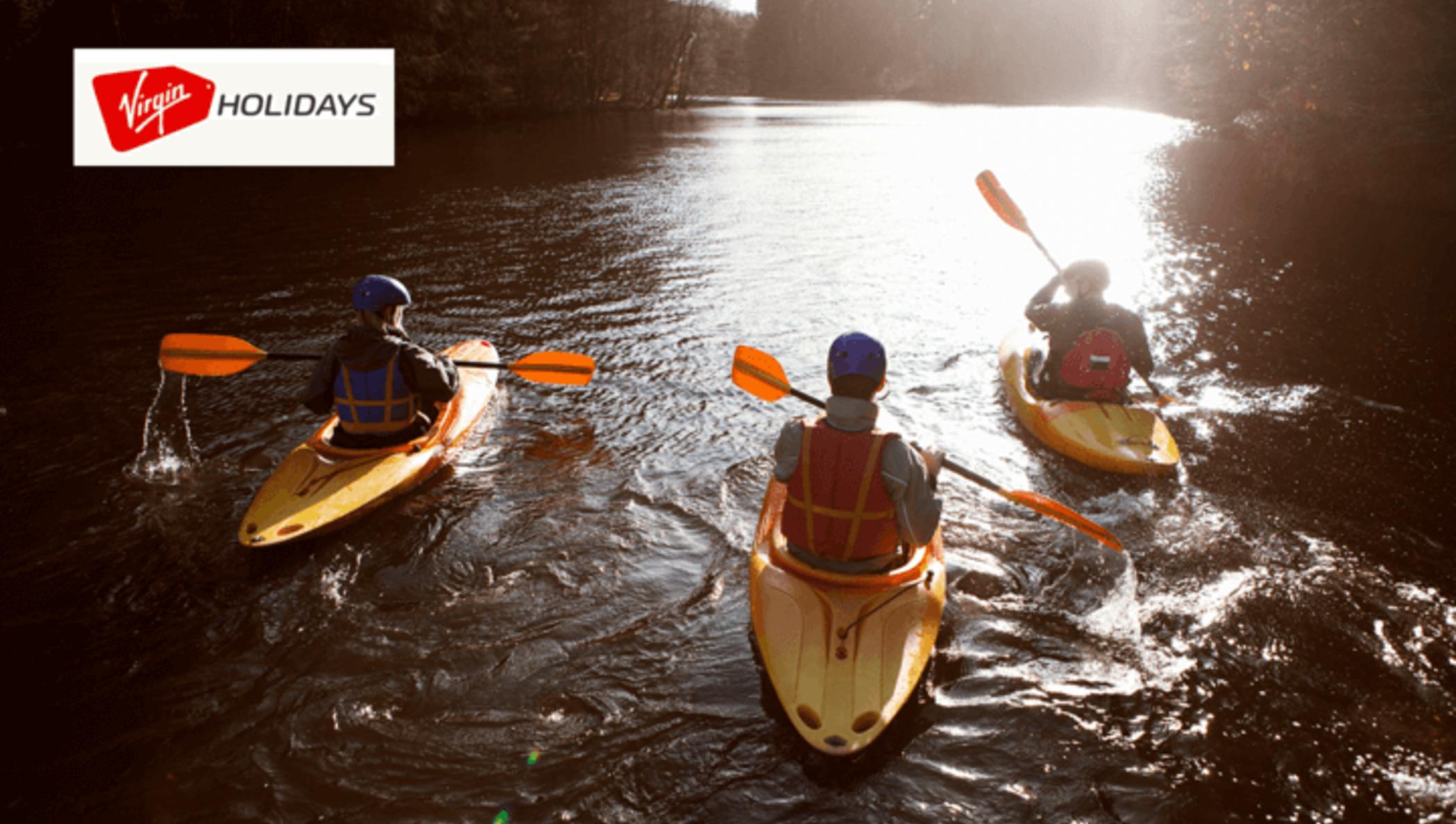 Des personnes font du kayak dans une rivière avec le logo Virgin Holidays dans le coin supérieur gauche.