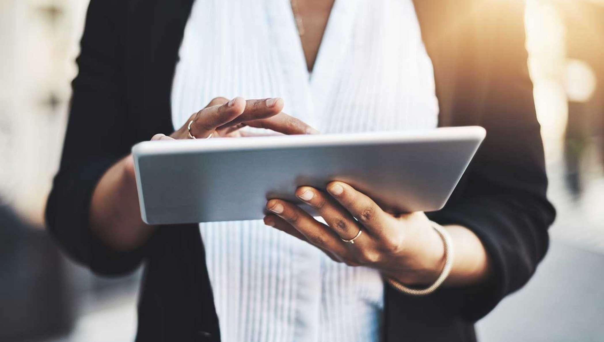 Une femme d'affaires consulte sa tablette pour trouver des informations sur un document à signer.