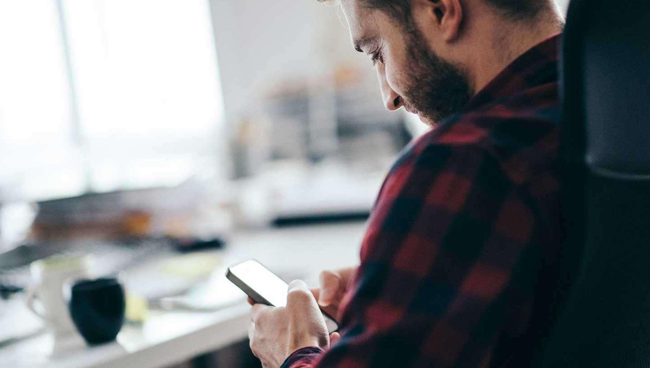 Un homme barbu vêtu d'une chemise en flanelle vérifie l'état d'un document à signer sur son téléphone portable.