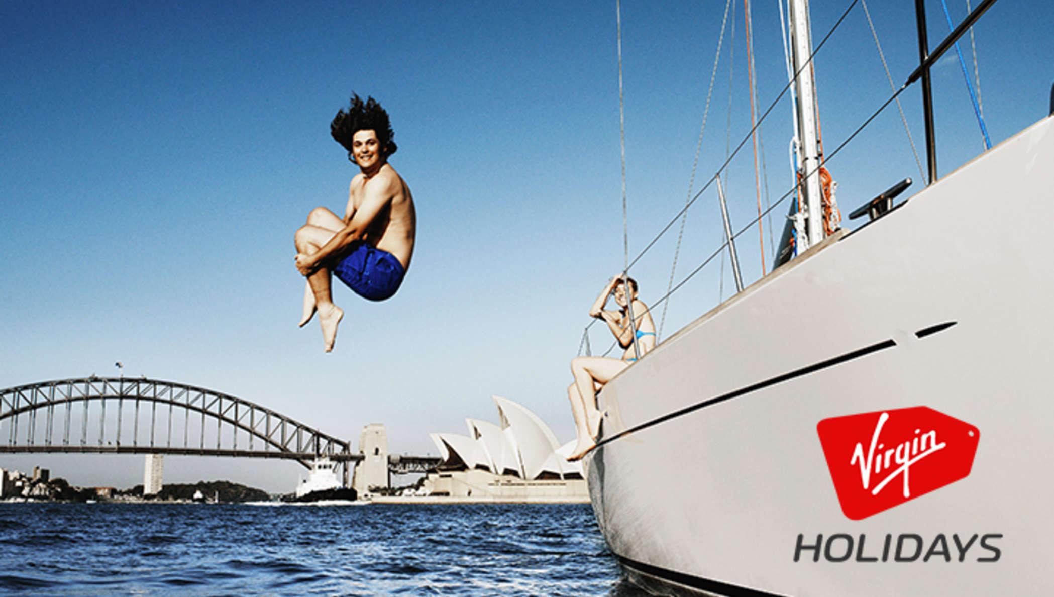 Un jeune homme sautant dans l'eau depuis un bateau