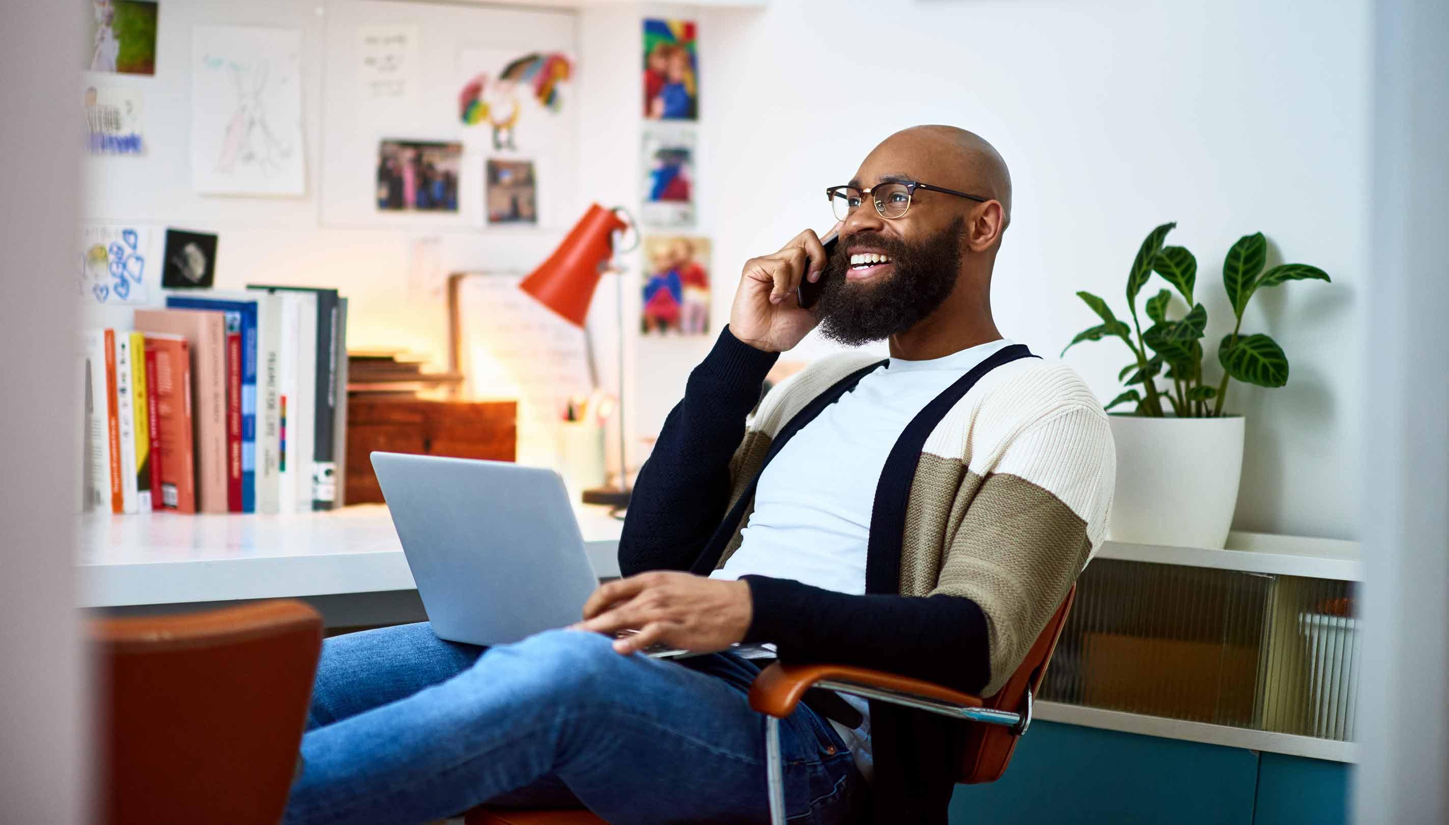 Un homme qui sourit alors qu'il travaille dans un bureau moderne à domicile.
